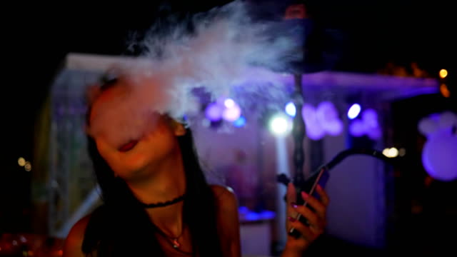 young woman smoke hookah and holding mobile on party in lights, close-up beautiful female inhales taste of tobacco video