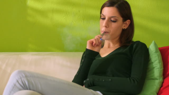 young woman smoking electronic cigarette at home video
