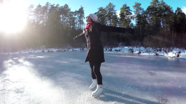 Young woman spinning on frozen lake on ice skates video