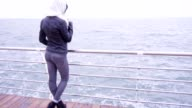 Young woman stand by the beach video