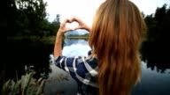 Young woman standing by the lake makes a heart shape finger frame on landscape video