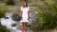 young woman standing in a lacy white dress video