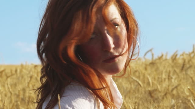 Young woman standing in a wheat video