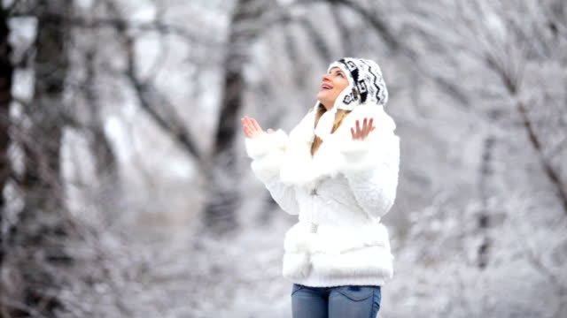 Young woman standing in the snowy forest. video