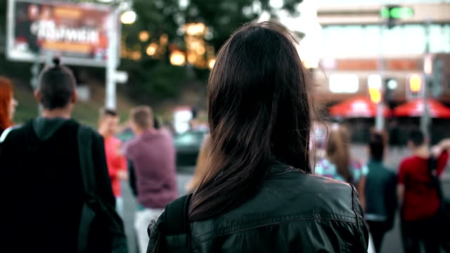 Young woman standing on street, preparing cross road at traffic lights, hair fluttering in the wind. Back view. Slow mo video