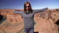 Young woman standing on the edge of the Grand Canyon video