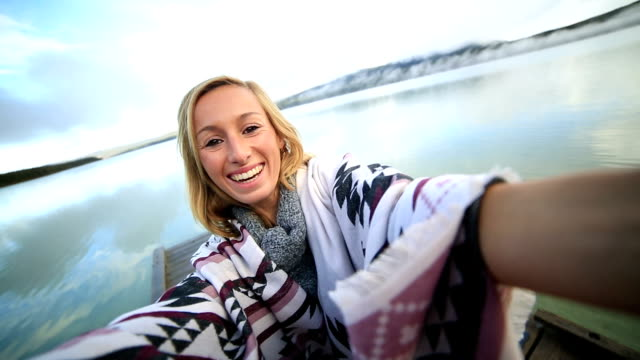 Young woman standing on wooden pier takes selfie portrait video