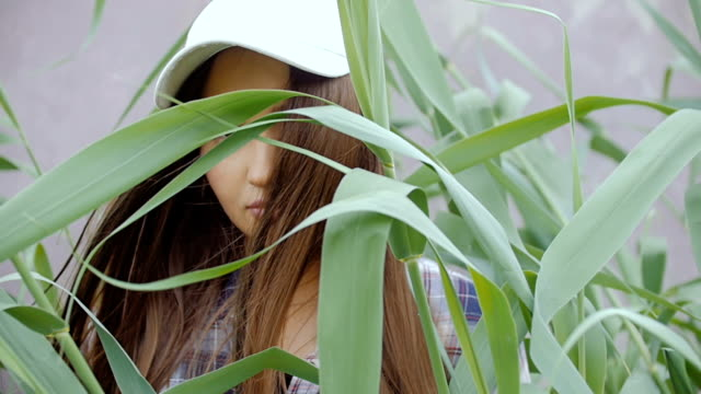 A young woman stands amongst the tall grass. S video