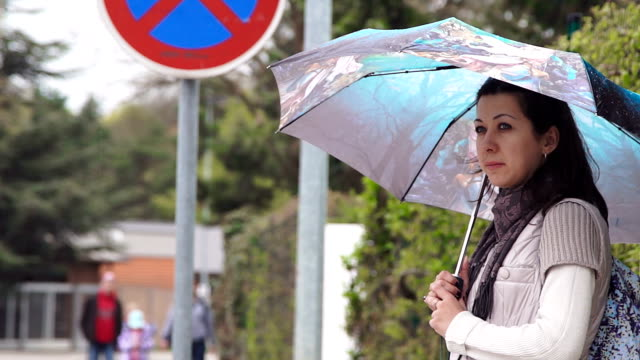 Young woman stands at the bus stop video