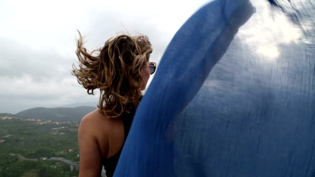 Young woman stands on rocky crest, scarf blowing in wind video