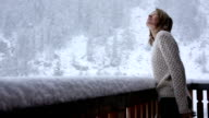 Young woman steps onto chalet veranda, watches snow flakes fall video