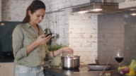Young Woman Stirs Food in Pan While Holding Her Smartphone and Smiling. video
