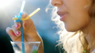 Young woman stirs the drink in the glass. In the picture visible lips and hair in which the sun shines. The concept - a heavenly vacation video