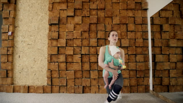 A young woman strengthens her leg muscles when fitness with a toddler video