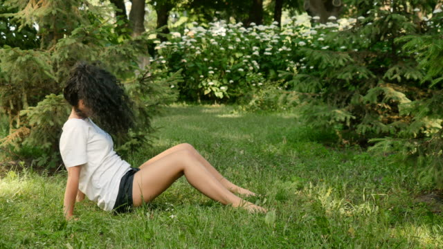 Young woman stretch her back at the park video