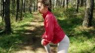 Young woman stretching in the forest video