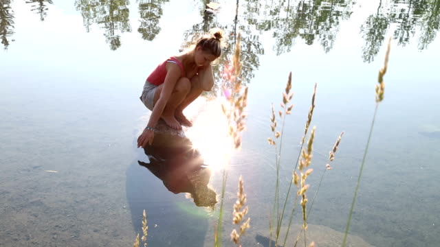Young woman strokes surface of mountain pond video