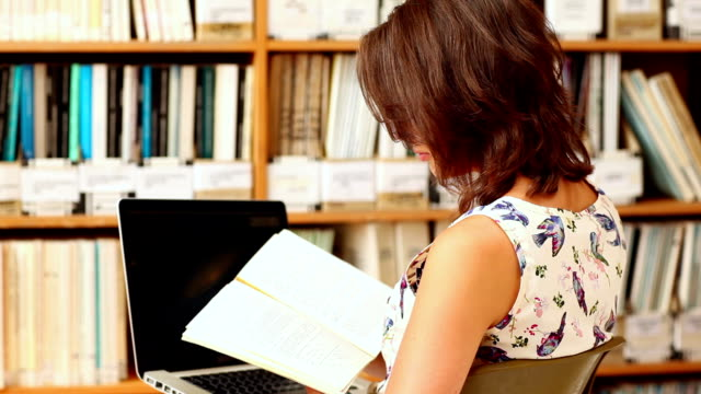 Young woman studying in library with laptop video
