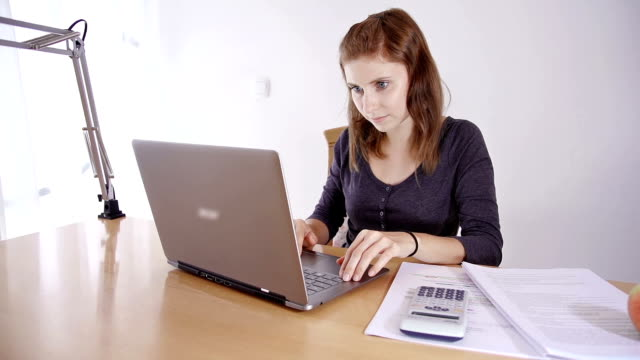 Young woman studying on laptop video