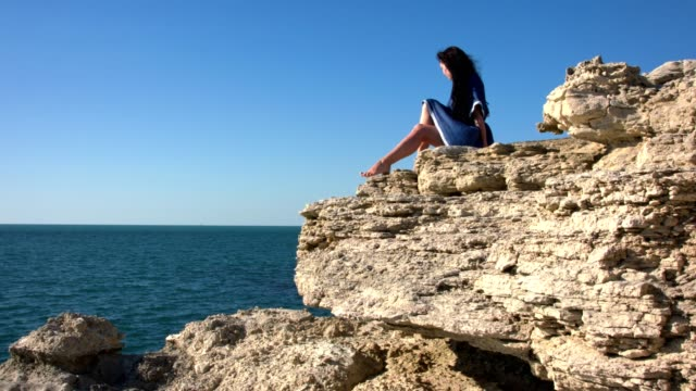 A young woman sunbathes on a rock. video