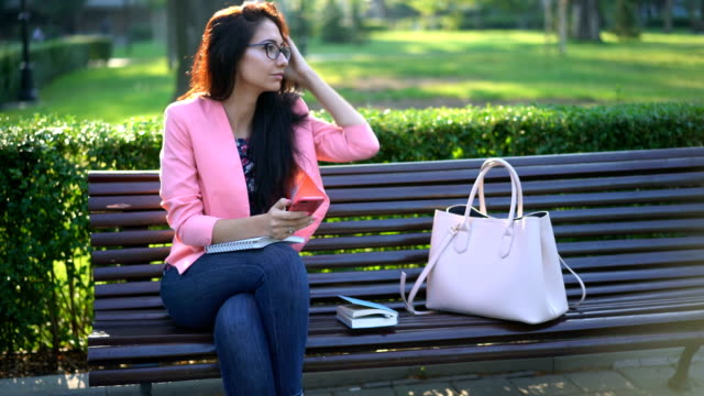 Young woman surfing the net on her mobile phone and relaxing in the park video