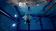 Young woman swimming in swimming pool video