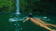 Young Woman Swimming to Waterfall video