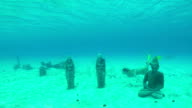 UNDERWATER CLOSE UP: Young woman swimming under the water surface, discovering sunken Buddha statue sanctuary in the middle of the ocean in crystal clear turquoise blue lagoon video