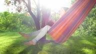 Young woman swinging on a hammock under the trees video
