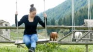 Young woman swinging on a swing in the countryside with horses in the background video