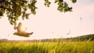 SLO MO Young woman swinging on tree swing video