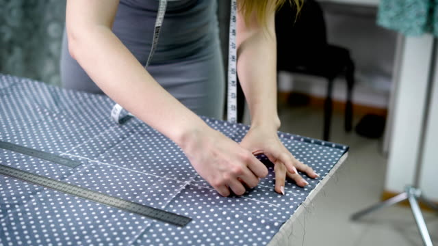 Young woman tailor drawing a pattern by piece of chalk on polka dots tissue video