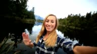 Young woman takes a selfie portrait by the lake video