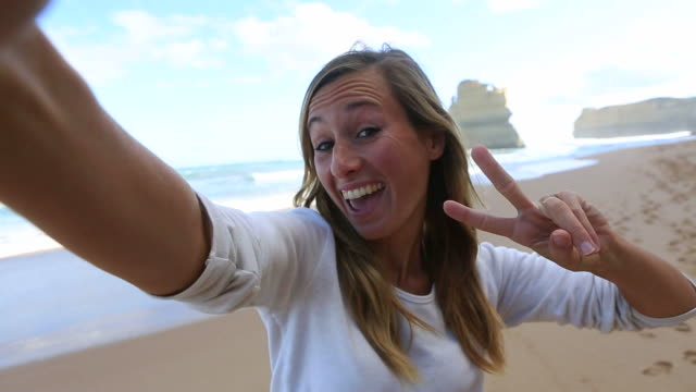 Young woman takes a selfie portrait on Gibsons steps beach video