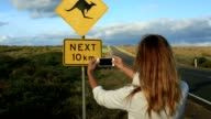 Young woman takes picture of kangaroo sign, Australia video