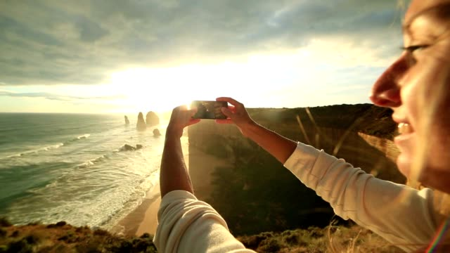 Young woman takes picture of Twelve Apostles using mobile phone video
