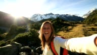 Young woman takes self portrait on mountain background video