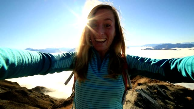 Young woman takes selfie on mountain summit video