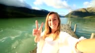 Young woman takes selfie on wooden jetty video