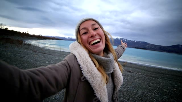 Young woman takes selfie portrait by the lake video