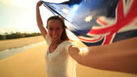 Young woman takes selfie portrait on beach with Australian flag video