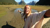 Young woman takes selfie portrait on mountain background video