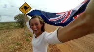 young woman takes selfie portrait on road next to kangaroo warning sign video