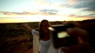 Young woman takes selfie portrait with spectacular landscape at sunrise video