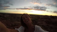 Young woman takes selfie portrait with spectacular landscape at sunrise-4K video