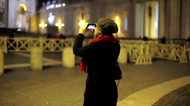 Young woman taking a photo with her cell phone camera while traveling video