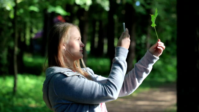 Young woman taking a picture of leaf. video