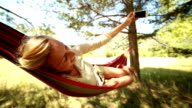 Young woman taking a selfie on hammock video