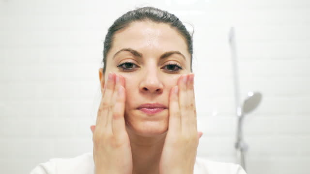 Young woman taking care of her skin. video
