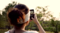 Young woman taking panorama pictures of sunset with her smartphone video